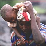 Congolese man carries young child